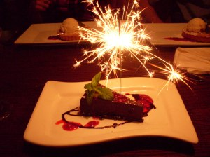 Chocolate flourless cake with birthday sparkler. This dense, fudge-like cake is best eaten with a good, strong cup of java.